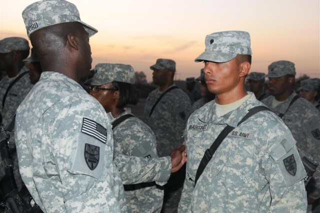 Sgt. 1st Class Freddie Raiford, platoon sergeant with the 159th Seaport Operations Company and a Miami native, affixes the 7th Sustainment Brigade combat patch on Spc. Roger Martinez, a motor transport operator and a San Antonio native, in a ceremony Oct. 19 at Joint Base Balad, Iraq.