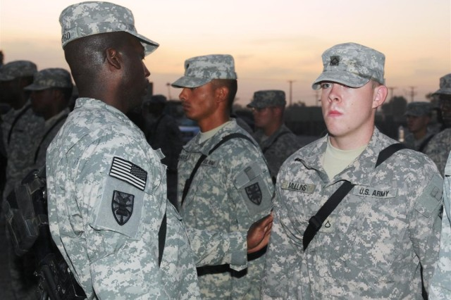 Sgt. 1st Class Freddie Raiford, platoon sergeant for the 159th Seaport Operations Company and a Miami native, affixes the 7th Sustainment Brigade combat patch on Pfc. Nathaniel Mullins, motor transport operator and a Tulsa, Okla., native, in a ceremony Oct. 19 at Joint Base Balad, Iraq.