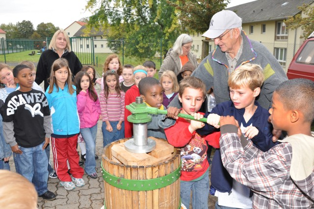 Dietrich KrAfAPger helps Aukamm Elementary School students operate an apple press to make fresh apple juice during a visit to the school Oct. 5.