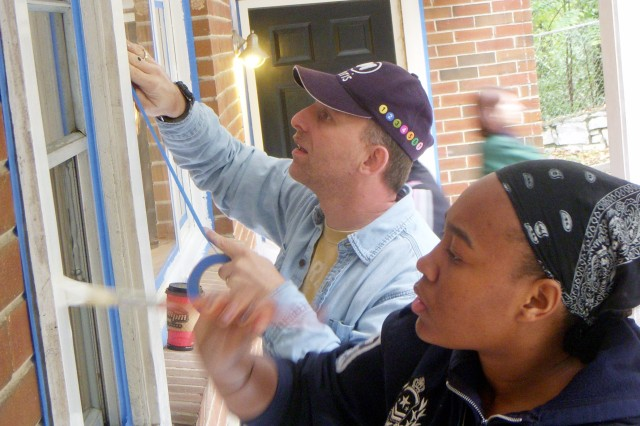 """Sgt. 1st Class Brad Helmick (rear), a contracting specialist for G-7, First Army, and Girl Scout Brionna Johnson (front), 15, paint window frames at the Shepherd Center Apartments during a """"Make a Difference"""" Day event Oct. 17. Helmick, Johnson and other members of the Fort McPherson, Fort Gillem and Atlanta communities volunteered their time and effort to help renovate the apartment complex, which houses servicemembers wounded in combat."""