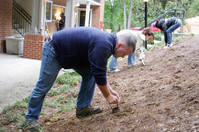 Chief Warrant Officer David Turner (left), an ammunition technician for G-4, Third Army/U.S. Army Central, and his wife, Debbie (right), dig holes in preparation for planting flowers in front of the  Shepherd Center Apartments.