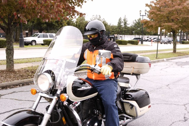 Sgt. Maj. Maurice King, chief National Guard enlisted advisor, U.S. Army Forces Command Headquarters, rides away on his motorcycle after the event. Like a safe rider, King is following proper safety procedures by wearing long pants and a jacket, a reflective vest, gloves, eye protection and a Department of Transportation approved safety helmet. Wearing the right personal protective equipment can mean the difference between life and death.