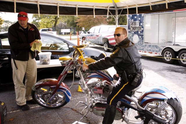 Henry County police officer Bruce LaBier takes a seat on the National Guard patriot chopper bike built by Orange County Choppers. The custum-built bike drew a lot of attention from the motorcyclists in attendance at the Motorcycle Safety Ride Oct. 16 at Fort Gillem.