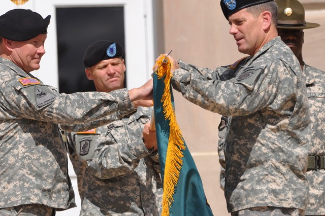 Gen. Martin Dempsey, left, commanding general of Training and Doctrine Command, and Maj. Gen. Michael Ferriter, Maneuver Center of Excellence commanding general, unfurl the MCOE colors while Command Sgt. Maj. Earl Rice, MCOE command sergeant major, holds the colors during the activation ceremony of the Maneuver Center of Excellence at Fort Benning's headquarters building Oct. 22.