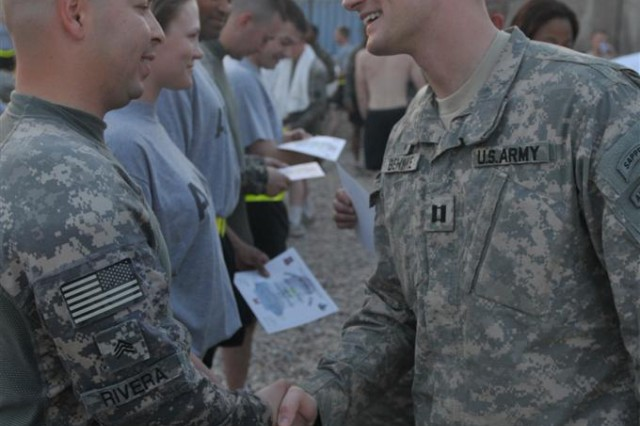 Sgt. Jedan Rivera, armorer with Headquarters and Headquarters Company, 37th Engineer Battalion, shakes hands with Capt. Timothy Behnke, the battalion chaplain for the 37th and a Wales, Wis., native, and receives a certificate of completion for the St. Michael's Jump Oct. 18 at the outdoor pool at Joint Base Balad, Iraq. The event is traditionally sponsored by the unit chaplain