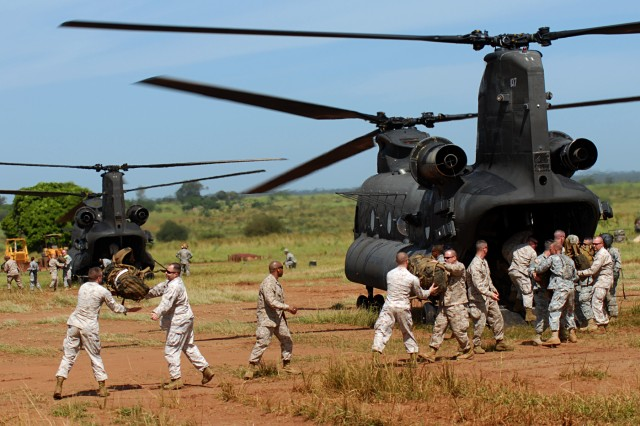 Servicemembers from Task Force Kitgum unload their baggage from a CH-47 Chinook helicopter Oct. 15. The servicemembers are participating in Natural Fire 10, a routine, scheduled training exercise, which offers an opportunity for East African Community Partner Nations and the U.S. military to work together on a humanitarian assistance mission.