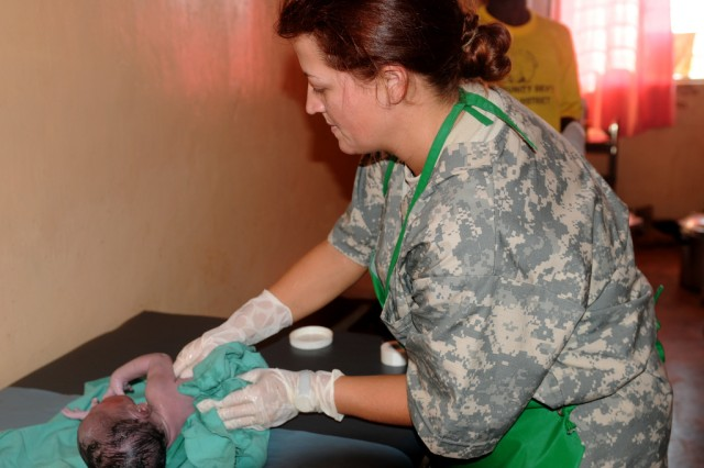 "KITGUM, Uganda - 1st Lt. Victoria Lynn Watson, an Army Reserve nurse deployed to Uganda with the 7225th Medical Support Unit (MSU), swaddles a newborn, October 20, 2009. Watson is a labor and delivery nurse in her civilian occupation and was asked to assist when the mother arrived at the Pajimo Clinic in an advanced stage of labor. She gave birth to a healthy, 5.5 lb. baby boy about 90 minutes later and asked Watson to name her son. Watson chose the name ""Cage."" The medical team was in Kitgum as part of Natural Fire, a multi-national military exercise focusing on humanitarian assistance, disaster response, and regional security."