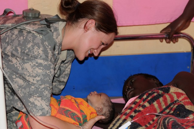 KITGUM, Uganda - Pfc. Kendra Hines, an Army Reserve medic from Lubbock, Texas, currently deployed with the 7225th Medical Support Unit (MSU) in northern Uganda, hands a newborn to his mother, October 20, 2009 in Kitgum, Uganda. The 19-year-old expectant mother arrived at the Pajimo Clinic in an advanced state of labor, and Hines was called upon to assist. The mother gave birth to a healthy, 5.5 lb. baby boy about 90 minutes later. The medical team was in Kitgum as part of Natural Fire, a multi-national military exercise focusing on humanitarian assistance, disaster response, and regional security.