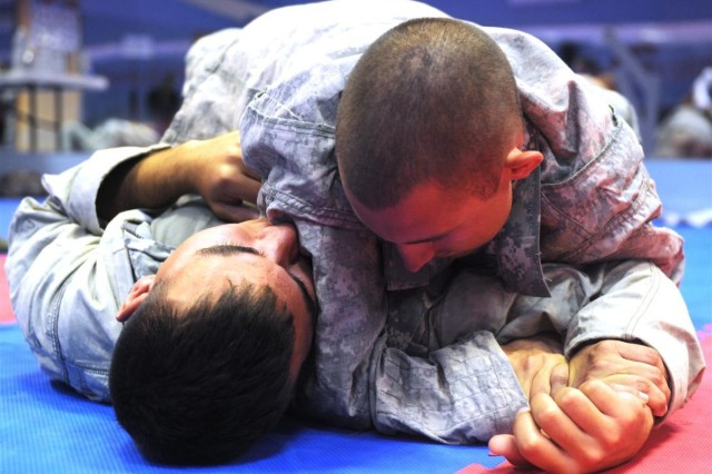 Pvt. Michael A. Perez, 287th Military Police Company out of Fort Riley, Kan., and a Clear Lake, Calif., native, and Spc. Elexander Hulinaty, also with the 287th, practice ground techniques during a combatives class Oct. 22. Perez and Hulinaty are stationed at Contingency Operating Location Warhorse, Iraq.