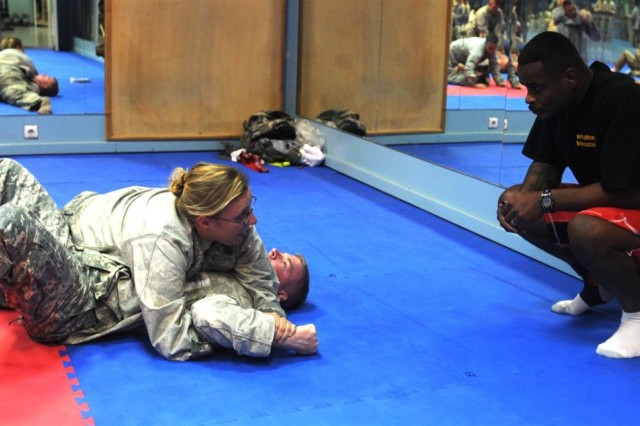 Senior Airman Catherine West, with the 532nd Expeditionary Security Forces Squadron and a Lumberton, N.C., native, explains each step of her takedown techniques to the instructor during the level one combatives class. This procedure is mandatory in order to pass.