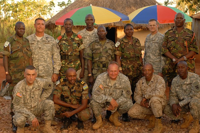 Senior enlisted advisors from the militaries participating in Natural Fire 10 assemble for a group photo at the 401st Infantry Brigade Canteen, Kitgum, Uganda, Oct. 20, 2009. From left to right the row is Command Sgt. Maj. David Wood, 21st Theater Sustainment Command, Warrant Officer Class 2 David Kalimba of Rwanda, Command Sgt. Major Lance Rygmyr, Task Force Kitgum, 1st Sgt. Oscar Jordan, Twin Cities Military Police Company, and Sgt. John Okumu, 21st Theater Sustainment Command. The second row is Warrant Officer Class 1 Sam Bakaise of Uganda, Sgt. Major Kelly Jack Luman, U.S. Army Africa, Warrant Officer Class 2 Serpe Nijungeko of Burundi, Command Sgt. Major Clifton Lewis, 21st Theater Sustainment Command, Warrant Officer Class 1 Charles Okello of Uganda, Warrant Officer Class 2 Angelina Mahawa of Tanzania, Command Sergeant Major Mark Ripka, U.S. Africa Command, and Warrant Officer Class 2 Ibraham Robow of Kenya.