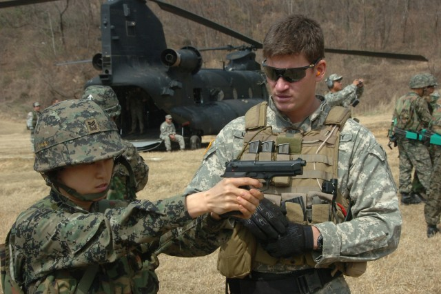 A Special Forces Soldier from the 1st Special Forces Group out of Fort Lewis, Wash., shows a Republic of Korea soldier the proper firing technique for an M-9 pistol during a training mission in South Korea, March 20.
