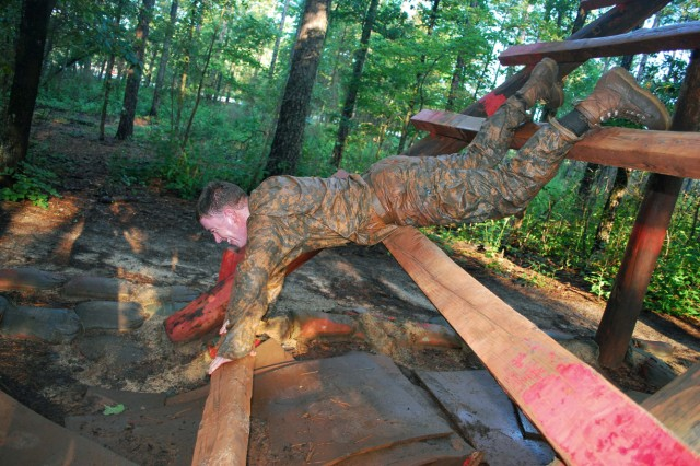 Spc. Christopher Darbyshire overcomes an obstacle during a readiness assessment for a tactical PSYOP detachment.