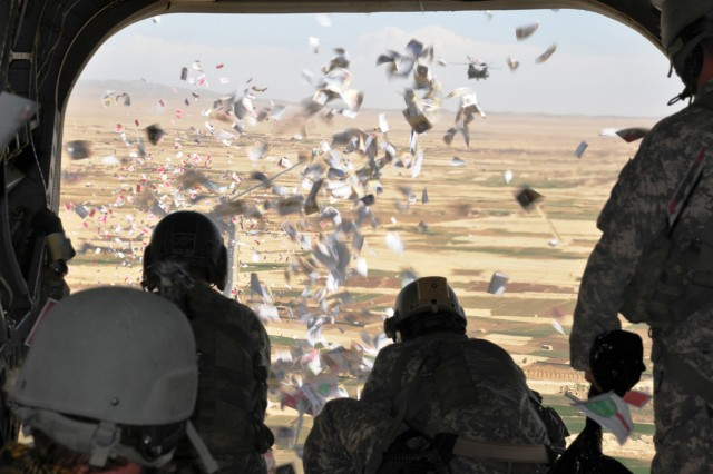 Soldiers from the 9th PSYOP Bn., 4th PSYOP Group, conduct a leaflet drop over a village in Iraq. PSYOP Soldiers use leaflets to disseminate important information to the local populace, including information about upcoming humanitarian assistance missions.