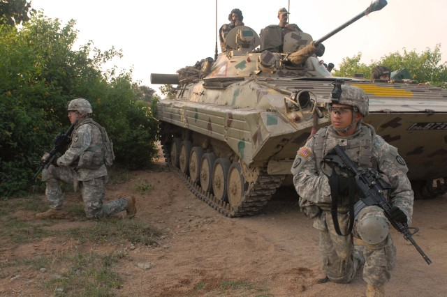(From left) Staff Sgt. Kris Jorgensen and Spc.  Jason Echevarria, both from 2nd Squadron, 14th Cavalry Regiment, 2nd Stryker Brigade Combat Team, 25th Infantry Division, from Schofield Barracks, Hawaii, maneuver with Indian soldiers in a Soviet-era amphibious tracked infantry fighting vehicle, during Exercise Yudh Abyas 09.