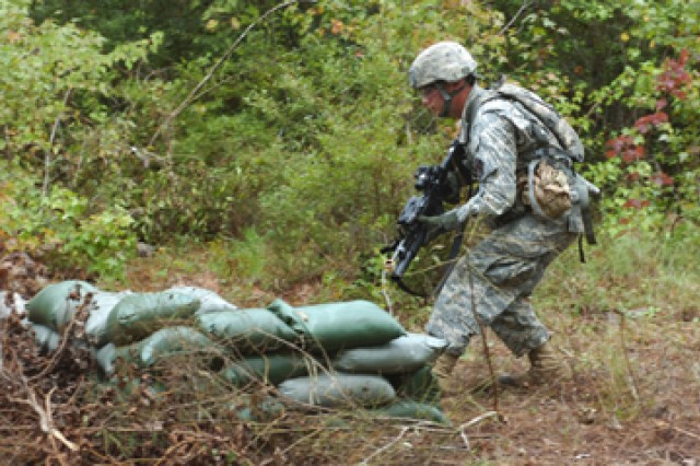 """Spc. Leo Krause, a squad leader assigned to 2nd Battalion, 30th Infantry Regiment, 4th Brigade Combat Team, 10th Mountain Division, takes cover from """"enemy"""" fire while negotiating a patrol lane during Expert Infantryman Badge testing on Fort"""