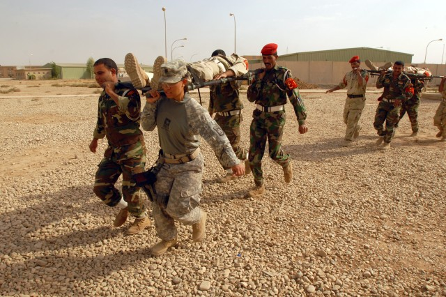 Staff Sgt. Monnet Bushner, from Humble, Texas, and a medic with the 218th Military Police Company from Fort Campbell, Ky., demonstrates how to carry a casualty on a stretcher with Iraqi military police from the 12th Iraqi Army Division, at K1 military base in Kirkuk province, Iraq, Oct. 13. The training was part of a series of classes on crowd control and medical tasks provided for the first time by the 218th MP Co. to the 12th IA MPs.