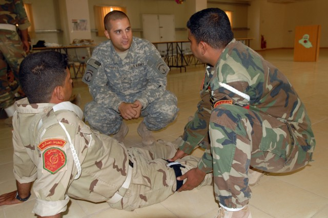 Pvt. Keith O'Connell, from Lawler, Iowa, and a medic with the 218th Military Police Company from Fort Campbell, Ky., instructs Iraqi military policemen from the 12th Iraqi Army Division on how to apply tourniquets, emergency trauma bandages, abdominal bandages and splints at K1 military base in Kirkuk province, Iraq, Oct. 13. The training was part of a series of classes on crowd control and medical tasks provided for the first time by the 218th MP Co. to the 12th IA MPs.