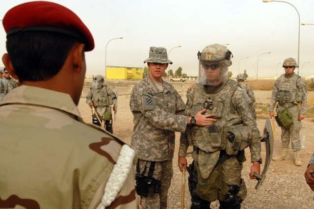 Sgt. Chris Murdoch (left), a Niantic, Conn. native and military police officer with the 218th Military Police Company from Fort Campbell, Ky., instructs Iraqi military police from the 12th Iraqi Army Division, on the different formations and equipment-like the shield and baton-are used during crowd control, at K1 military base in Kirkuk province, Iraq, Oct. 13. The training was part of a series of classes on crowd control and medical tasks provided for the first time by the 218th MP Co. to the 12th IA MPs.