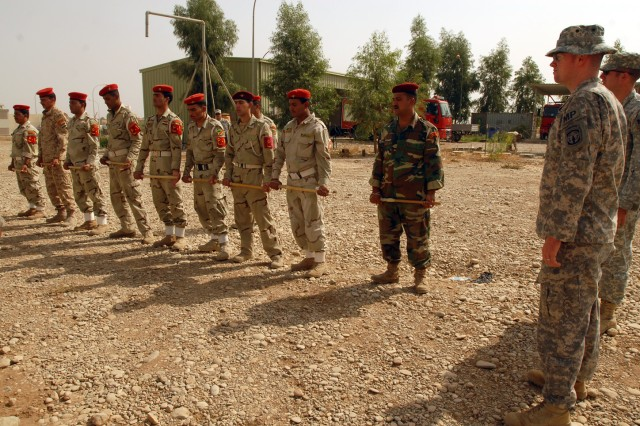 Sgt. Chris Murdoch (right), a Niantic, Conn. native and military police officer with the 218th Military Police Company from Fort Campbell, Ky., instructs Iraqi military police from the 12th Iraqi Army Division, on using a baton and moving toward a crowd during a crowd control class at K1 military base in Kirkuk province, Iraq, Oct. 13. The training was part of a series of classes on crowd control and medical tasks provided for the first time by the 218th MP Co. to the 12th IA MPs.