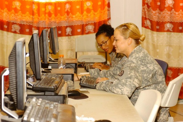 Private First Class Tiffany Gordon (far seat) and Pfc. Jill Logan, paralegal specialists, HHOC, 25th CAB, 25th Inf. Div., work on their on-line courses at the computer lab in the Contingency Operating Base Speicher Education Center, COB Speicher, Oct. 15. (Army photo by: Staff Sgt. Mike Alberts  25th Combat Aviation Brigade Public Affairs)