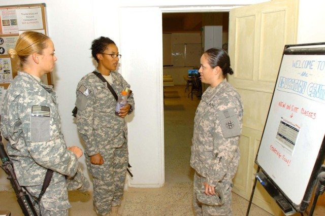 Private First Class Jill Logan (left) and Pfc. Tiffany Gordon (center), paralegal specialists, HHOC, 25th CAB, 25th Inf. Div., discuss financing on-line classes with 1st Lt. Maricela Cantu, COB Speicher education officer, 211th Regional Support Group, an Army reserve unit from Corpus Christi, Texas, at the COB Speicher Education Center, Oct. 15.