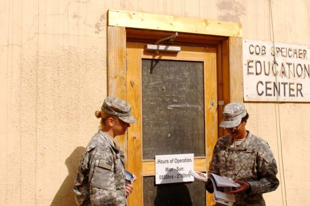 Private First Class Jill Logan (left), and Pfc. Tiffany Gordon, paralegal specialists, HHOC, 25th CAB, 25th Inf. Div., stand outside of the Contingency Operating Base Speicher Education Center discussing coursework, Oct. 15. (Army photo by: Staff Sgt. Mike Alberts  25th Combat Aviation Brigade Public Affairs)