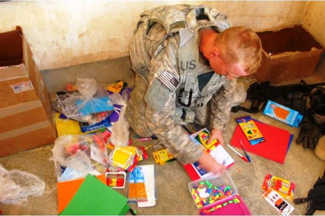 Sgt. Jonathon Chambers, a Streator, Ill. native with 1st Battalion, 8th Cavalry Regiment, 2nd Brigade Combat Team, 1st Cavalry Division, helps separate school supplies during a school supply delivery to the Baghara Elementary School in Hawijah, Kirkuk province, Iraq, Oct. 18. The supplies were provided by J.E. Ober Elementary School students in Garrett, Ind., after Staff Sgt. Jared Wiegand, a Fort Wayne, Ind. native also with 1st Bn., 8th Cav Regt., visited the school last March, where his sister-in-law teaches.