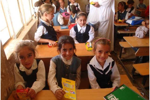 Iraqi schoolchildren from Baghara Elementary School in Hawijah, Kirkuk province, Iraq, smile excitedly after receiving school supplies during a school supply delivery by 1st Battalion, 8th Cavalry Regiment, 2nd Brigade Combat Team, 1st Cavalry Division, Oct. 18. The supplies were provided by J.E. Ober Elementary School students in Garrett, Ind., after Staff Sgt. Jared Wiegand, a Fort Wayne, Ind. native with 1st Bn., 8th Cav Regt., visited the school last March, where his sister-in-law teaches.