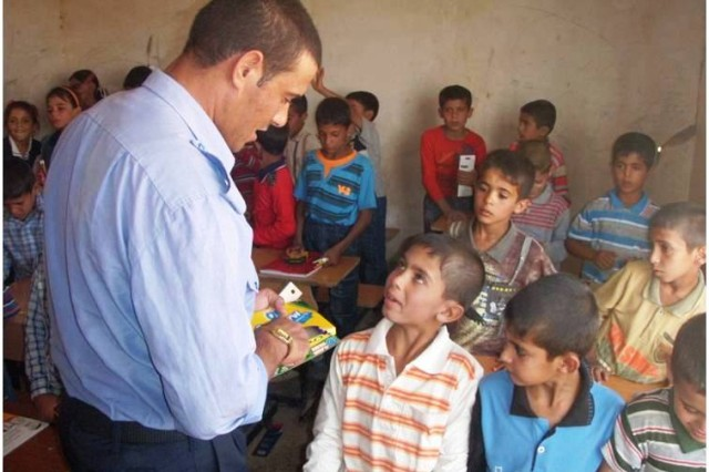 An Iraqi police officer assists Soldiers from the 1st Battalion, 8th Cavalry Regiment, 2nd Brigade Combat Team, 1st Cavalry Division, to distribute school supplies to the Baghara Elementary School in Hawijah, Kirkuk province, Iraq, Oct. 18. The supplies were provided by J.E. Ober Elementary School students in Garrett, Ind., after Staff Sgt. Jared Wiegand, a Fort Wayne, Ind. native with 1st Bn., 8th Cav Regt., visited the school last March, where his sister-in-law teaches.