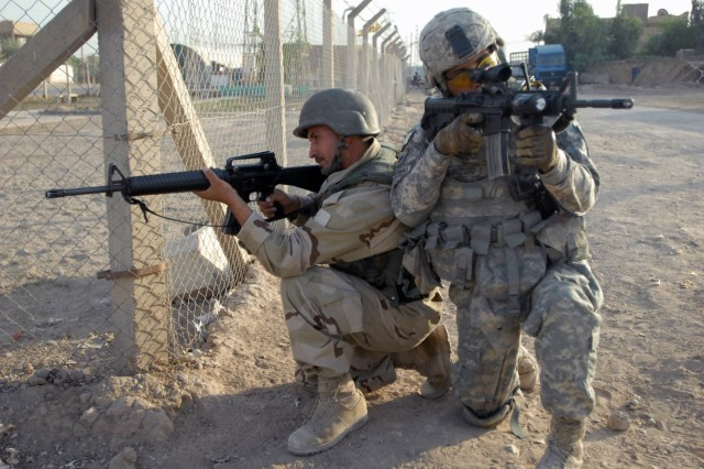 BAGHDAD - El Paso, Texas native, Staff Sgt. Eric Campuzano (right), pulls security with one of the Warrior Academy Soldiers (left) from the 2nd Battalion, 44th Brigade Iraqi Army Division while on patrol in Baghdad Oct. 20.