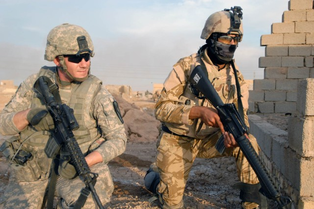 BAGHDAD - Moore, Okla. native ,Cpl. Christopher Cannon (left), a basic rifle marksmanship instructor, pulls security with one of the Soldiers from the 2nd Battalion, 44th Brigade, Iraqi Army Division while on patrol in Baghdad, Oct. 20.