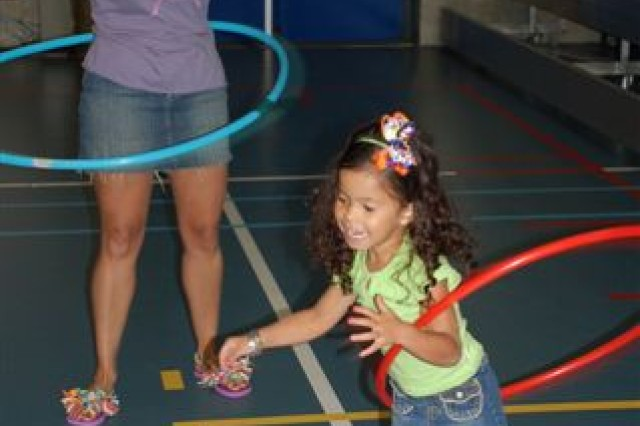 """Military mom Sianda Ruiz and three-year old daughter, Niobe Ruiz try out the hula hoops during USAG Schinnen's Thursday morning Play Group. Ruiz brings Niobe to Play Group """"so she can burn some energy and socialize with lots of other kids her"""