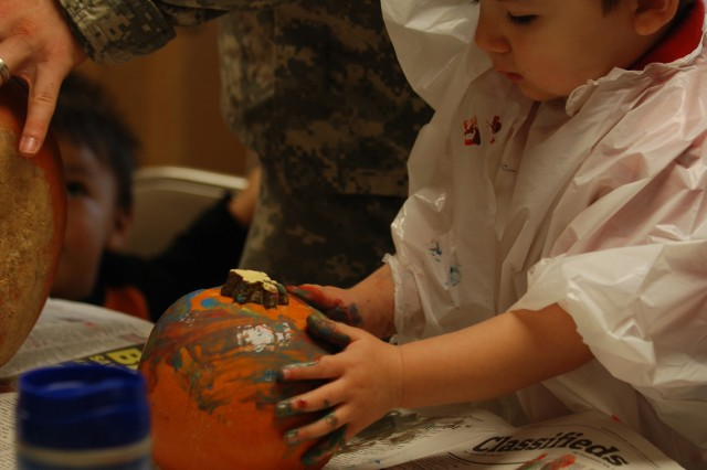 Krystofer Busch, 2, paints a pumpkin during a Halloween event on Oct. 23 sponsored by the Family Readiness Group. Krystofer's parents are Sgt. Martin Busch of Headquarters Company, 2nd Brigade Combat Team, 82nd Airborne Division, and Mary Busch. The purpose of the FRG is to provide support and raise the morale of soldiers and family members, and serve as a chain of communication during times of deployment. (U.S. Army photo by Pfc. Kissta M. Feldner, 2nd BCT, 82D ABN DIV PAO)