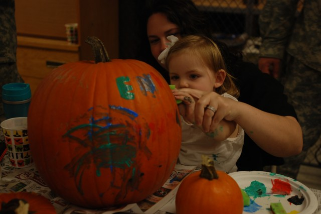Jeren Tollefson helps her daughter, Emilia, 19 months, paint a pumpkin during a Halloween event on Oct. 23 sponsored by the Family Readiness Group. Emilia's father, Lt. Andrew Tollefson, is assigned to Headquarters Company, 2nd Brigade Combat Team, 82nd Airborne Division. The purpose of the FRG is to provide support and raise the morale of soldiers and family members, and serve as a chain of communication during times of deployment. (U.S. Army photo by Pfc. Kissta M. Feldner,2nd BCT, 82D ABN DIV PAO)