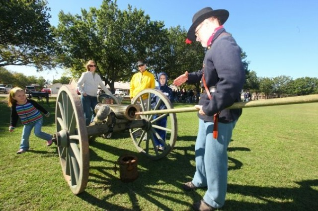 Clive Siegle, member of the Fort Sill Museum Gun Detachment, demonstrates how a worm is used to clear a howitzer to the Boyle family. Dozens of families visited the fort Oct. 27 to see history come to life.