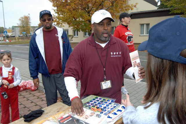 Sam Chism, a camp director and mentor with the Ramstein Drug Education for Youth, passes out information to spectators Oct. 24 at the U.S. Army Garrison Kaiserslautern's Red Ribbon Run on Rhine Ordnance Barracks. Many organizations and agencies had information booths as a way to show community support for a drug-free community. Drug Education For Youth is a self-esteem building program that provides kids with the tools they need to resist drugs, gangs and alcohol.