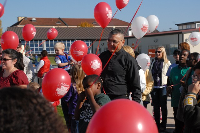USAG Vicenza Deputy Garrison Chaplain (Maj.) Jose Herrera makes his way through a throng of balloons Oct 25 at Vicenza's Hoekstra Field where community members gathered for a balloon release in honor of Red Ribbon Week. Hundreds of balloons with drug-free messages in English and Italian were released.  The event was one of many at Caserma Ederle in honor of Red Ribbon Week, an educational campaign that promotes drug-free lifestyles.