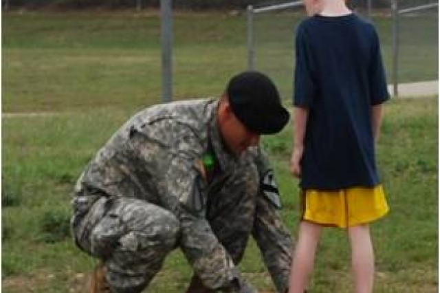 "A Soldier, assigned to 2nd Battalion, 12th Cavalry Regiment, 4th Brigade Combat Team, 1st Cavalry Division ""Long Knives,"" ties a Reeces Creek Elementary School student's shoe during the school's Annual Freedom Walk Sept. 18."