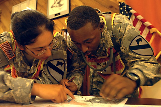 Spcs. Victoria Caldera (left) and Marcus Gray, of Company D, Forward Support Battalion, 1st Squadron, 9th Cavalry Regiment, 4th BCT, 1st Cav. Div., work together to plot their points before heading out to the land navigation site Oct. 21, during the Spur Ride on Fort Hood.