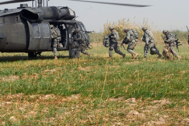 TAJI, Iraq- American Soldiers sprint up to a UH-60 Blackhawk helicopter during a combined air assault mission, Oct. 26, north of Baghdad.