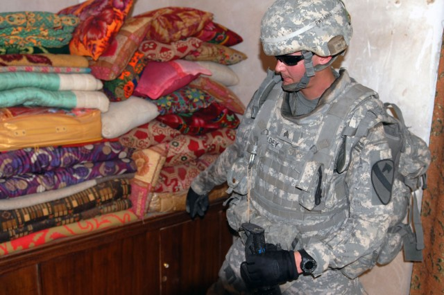 TAJI, Iraq- Killeen, Texas native, Sgt. John Goldey, an armor crewman attached searches for weapons in a stack of blankets during a combined air assault mission, here, Oct. 26.