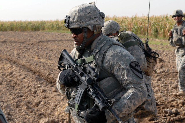 TAJI, Iraq- Killeen, Texas native, Spc. Timothy Tanner, an armor crewman attached to the 1st Battalion, 82nd Field Artillery Regiment, 1st Brigade Combat Team, 1st Cavalry Division, patrols with his squad through a field during a combined air assault mission, here, Oct. 26.