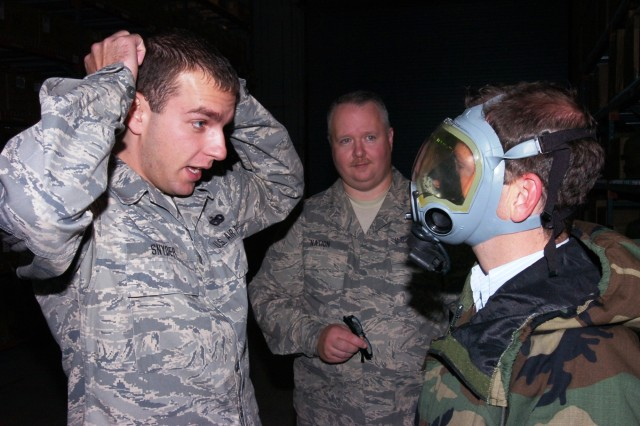 Air National Guardsman Tech Sgt. Jason Snyder, Mobility Element section  and Master Sgt. Robert Nation, Material Management Superintendent demonstrate the proper way to seal a Chemical Protective Mask and wear Joint Service Lightweight Integrated Suit Technology (JSLIST) during an Honorary Commanders Association event recently in Pittsburgh. The HCA is composed of local Chamber of Commerce members and servicemembers from the 316th Expeditionary Sustainment Command, the 911th Air Wing, and the 171st ARW.