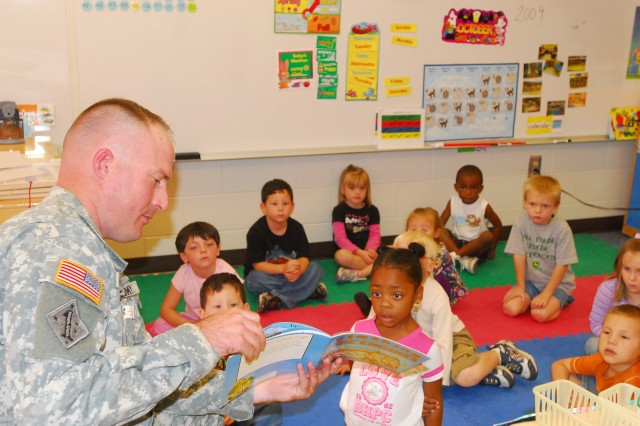 Sergeant William Krauser, HHC, 4th IBCT, 3rd ID, reads to kindergarten students at Kessler Elementary School at Fort Stewart as part of the Vanguard Brigade's 'Make a Difference Day' program, Oct. 21.