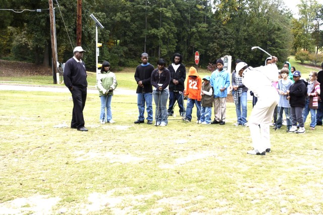 Chris Hawkins, assistant instructor, First Tee of Atlanta, shows students how to drive a ball down range during golfing lessons held at The Commons at Fort McPherson Saturday as First Tee Head Instructor William Lewis (far left, in black) observes. In partnership with the DoD, First Tee of Atlanta is teaching military children ages 7 through 17 the fundamentals of golf.
