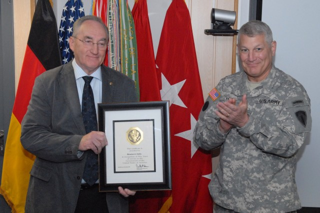"WIESBADEN, Germany (October 29, 2009) -- Gen. Carter Ham (right), commander, U.S. Army Europe, applaudes Winston A. Hollis in 5th Signal's conference room, after he was presented with a 50-years of U.S. government service certificate by Ham. ""We have a very capable and dedicated civilian work force who are just as dedicated as military Soldiers,"" said Ham. Hollis has served the last 11 years in 5th Signal as a logistics managementspecialist. (Photo by Kristopher Joseph, 5th Signal Command)"