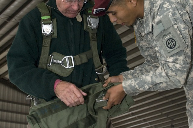 Civic leader, Jonathan Brookshire, learns how to don a T-10 parachute from a 2nd Brigade Combat Team, 82nd Airborne Division, paratrooper at Pope Air Force Base Oct. 27. During a joint forcible entry exercise, a group of civic leaders were invited to witness some of the key capabilities of the XVIII Airborne Corps at Fort Bragg, N.C., Oct. 27-30.