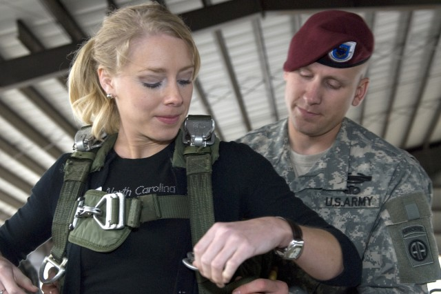 Miss North Carolina, Katherine Southard, gets some help from a paratrooper with 2nd Brigade Combat, 82nd Airborne Division, while donning a T-10 parachute at Pope Air Force Base, N.C., Oct. 27. Southard and other local civic leaders visited the Pope AFB and Fort Bragg areas to witness some of the key capabilities of XVIII Airborne Corps during a joint forcible entry exercise, Oct. 27 through 30.