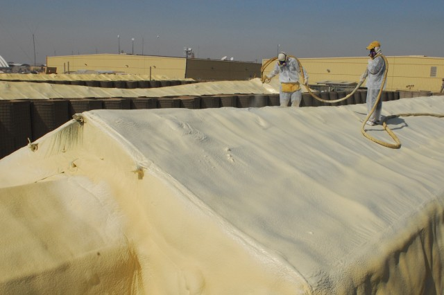 Butch Kline, foam team 1 leader, and his assistant Hamed, an Iraqi working on the project, apply the Terra Strong spray foam on the roof of a Contingency Operating Base Basra Medical Center tent Oct. 17.